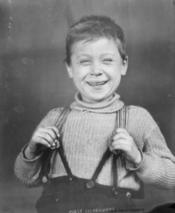 Boy with a big smile, holding his suspenders