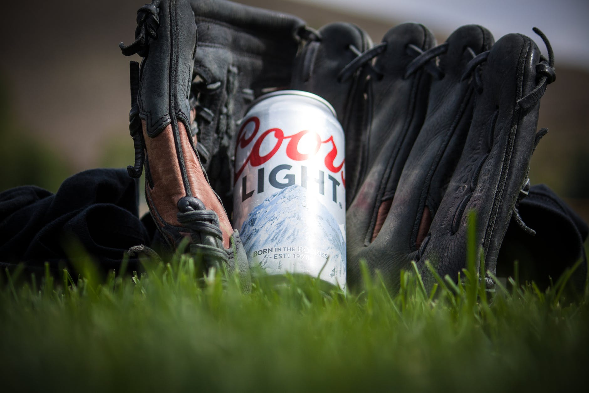 close up photography of coors light beer near black baseball mitts